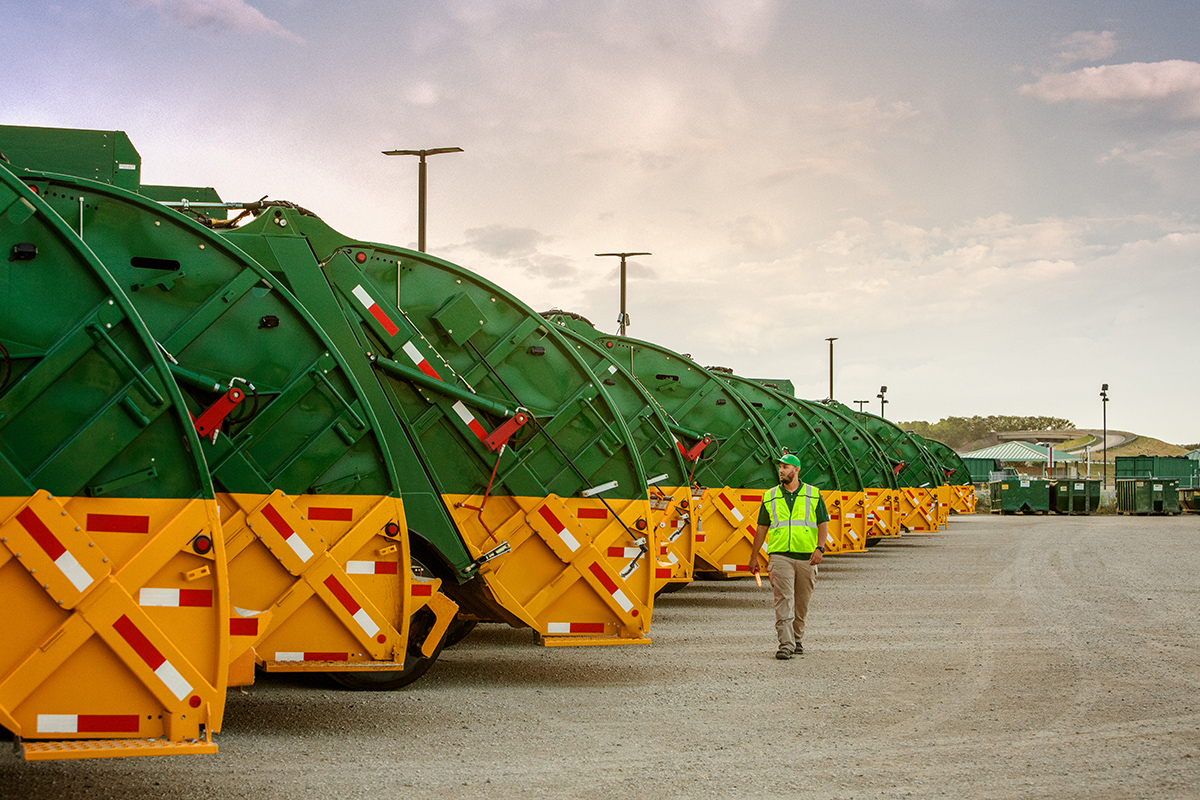 A man wearing a reflective vest looks at a fleet of Waste Management garbage trucks as he walks past them.